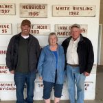 Jon Sauer, Karen Sauer and Mike Sauer stand in front of signs from Red Willow Vineyard.